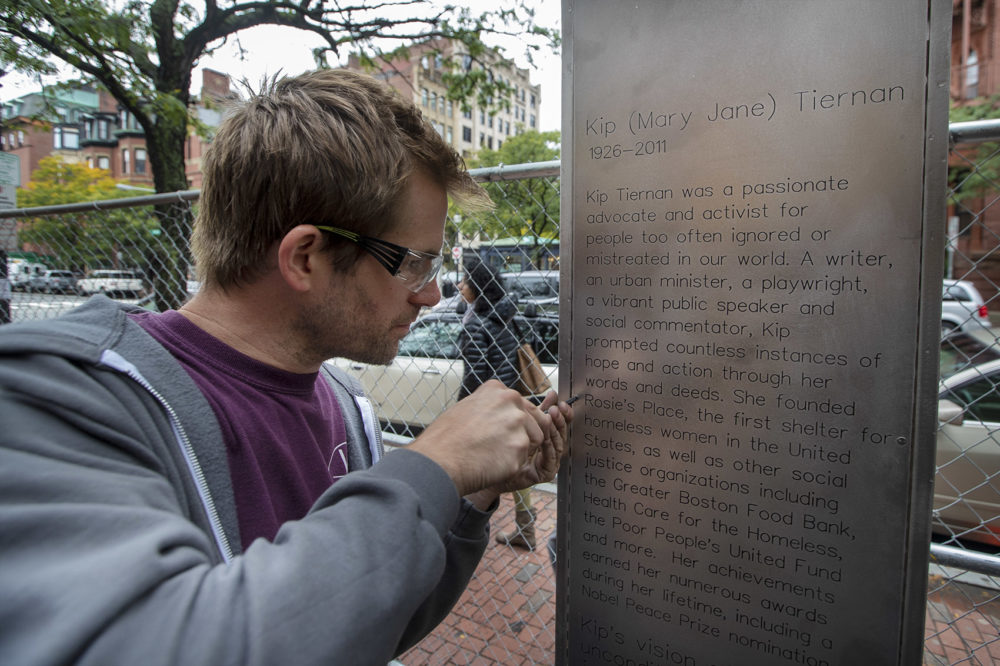 Jackson Morley fastens a panel with Kip Tiernan's biography on it into place on the memorial honoring her being built on Dartmouth Street. (Jesse Costa/WBUR)