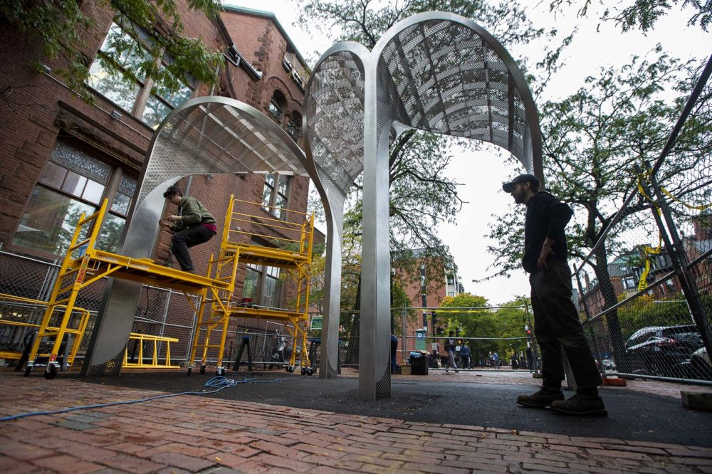 Workers from Whetstone Workshop place the finishing touches on to the Kip Tiernan Memorial on Dartmouth Street in Copley Square. (Jesse Costa/WBUR)