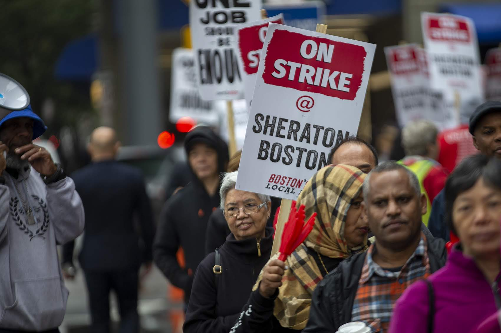 "Mei Leung, left of the ""On Strike"" sign, a housekeeper at the Sheraton Boston, has been picketing regularly in front of the hotel. (Jesse Costa/WBUR)"