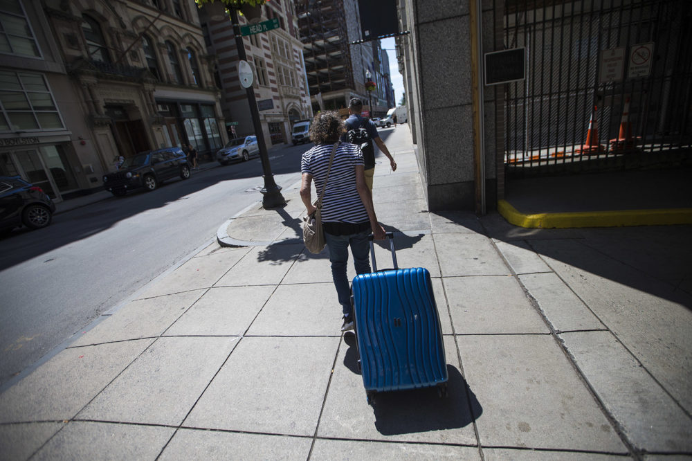 Nancy, who came to Boston for shelter and services after becoming homeless in November, pulls her belongings in a suitcase outside St. Francis House in July. (Jesse Costa/WBUR)