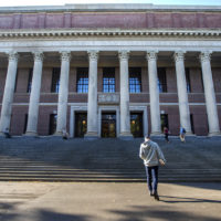 Student walk in and out of the Widener Library in Harvard Yard. (Jesse Costa/WBUR)