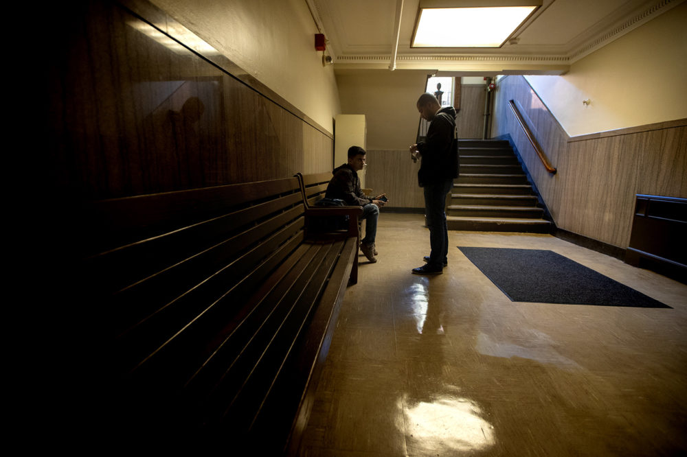 Diego Pizarro stops to talk with a young man in East Boston District Court. (Jesse Costa/WBUR)