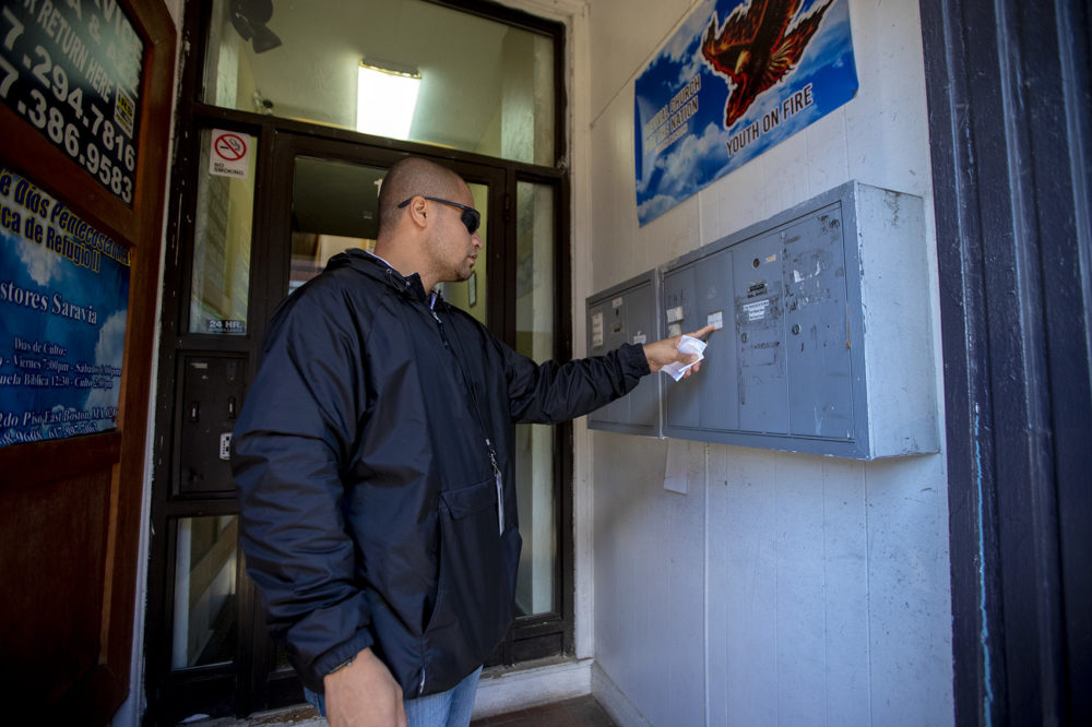 Diego Pizarro looks at mailboxes at a East Boston apartment building, only to find out all the occupants of the building are all businesses. (Jesse Costa/WBUR)