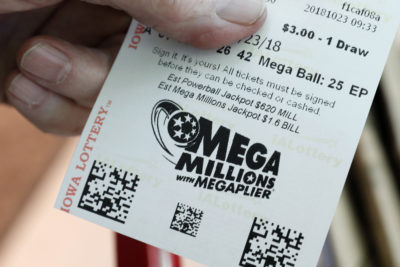 A customer shows his Mega Millions lottery ticket at a local grocery store on Tuesday in Des Moines, Iowa. (Charlie Neibergall/AP)
