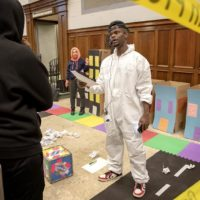 "Artist Tory Bullock challenges a contestant to answer a question in ""The Gentrification Game."" (Robin Lubbock/WBUR)"