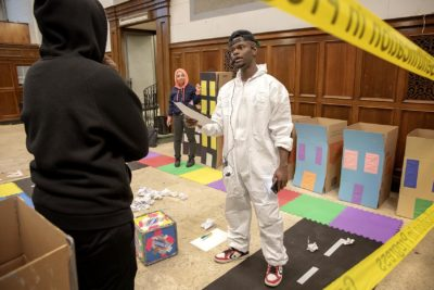 """Artist Tory Bullock challenges a contestant to answer a question in """"The Gentrification Game."""" (Robin Lubbock/WBUR)"""