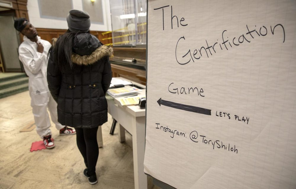 "Artist Tory Bullock invites a contestant to play ""The Gentrification Game."" (Robin Lubbock/WBUR)"