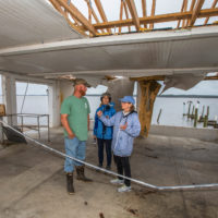 Here & Now's Robin Young, right, and Karyn Miller-Medzon interview T.J. Ward at his oyster processing facility that was gutted by Hurricane Michael in Apalachicola, Fla. (Mark Wallheiser for Here & Now)