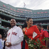 Baseball Hall of Fame member and former Boston Red Sox player Pedro Martinez, left, walks off the field with his wife, Carolina, during a ceremony where his jersey was retired prior to a baseball game against the Chicago White Sox at Fenway Park in Boston, July 28, 2015. (Charles Krupa/AP)