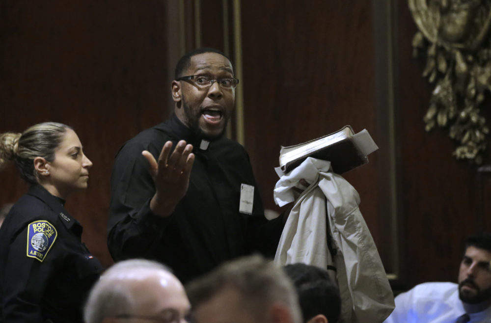 Rev. Darrell Hamilton, right, a pastor at First Baptist Church, in Boston, is escorted away by a Boston police officer, left, after interrupting remarks by Attorney General Jeff Sessions. (Steven Senne/AP)