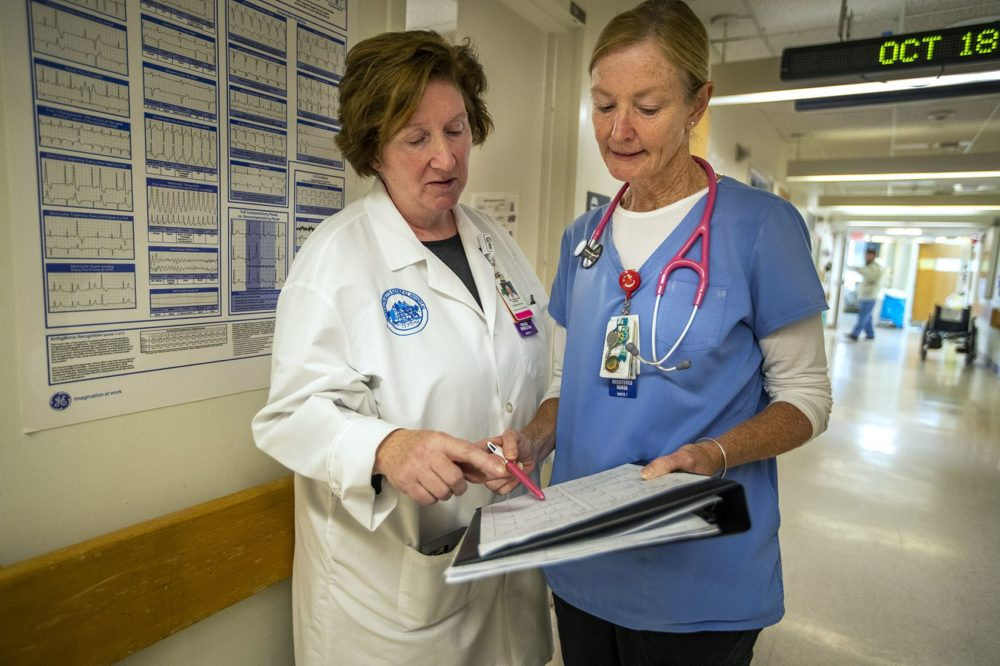 Theresa Capodilupo, a nurse director and Brenda Pignone, a bedside nurse, review the daily patient assignment sheet for a post-surgery and trauma unit at Massachusetts General Hospital. They, like other nurses in the state, are watching Question 1 closely. (Jesse Costa/WBUR)