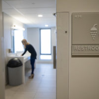Chloe Strange, who supervises RAs in UMass Boston's new dorm, uses a wash basin in an open concept, all-inclusive bathroom. The bathroom features private rooms with showers and toilets. (Jesse Costa/WBUR)