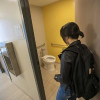 UMass Boston student Chanel An enters one of the toilet and shower rooms in the open concept, all-inclusive bathroom at a new dorm building. (Jesse Costa/WBUR)