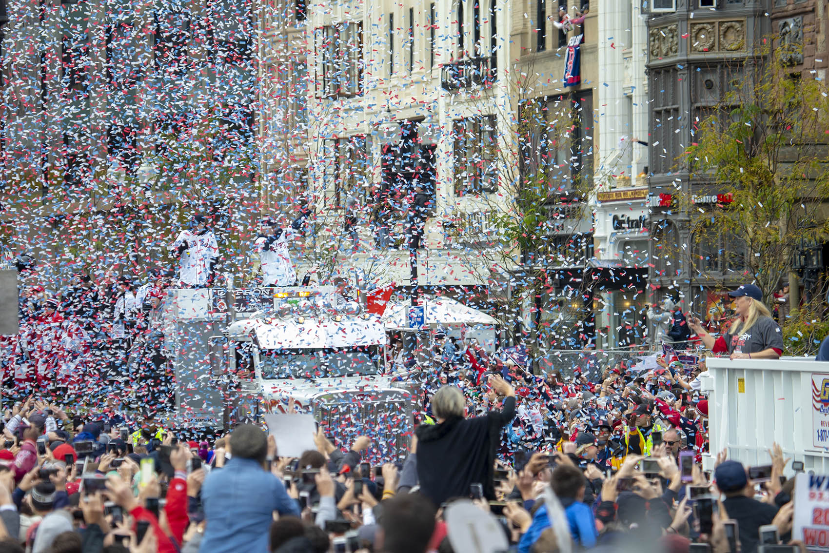 Fans cheer and confetti flies in the air as the Red Sox World Series victory Rolling Rally enters Copley Square on Boylston Street. (Jesse Costa/WBUR)
