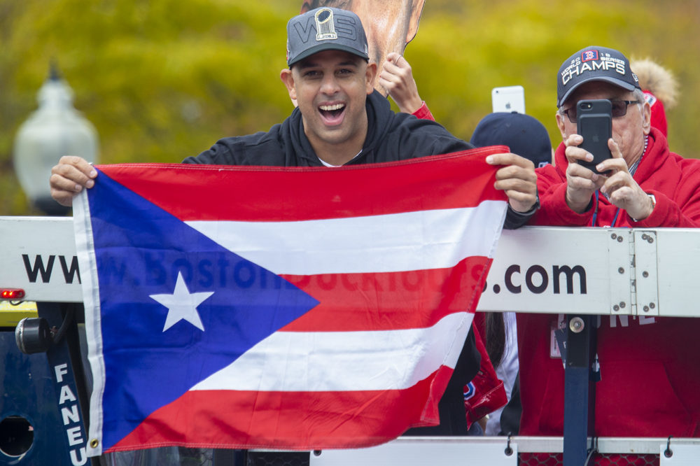 Red Sox manager Alex Cora holds up a flag from his native home of Puerto Rico. (Jesse Costa/WBUR)