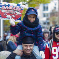 Six-year-old Jazmyn Pollanco sits on her dad's shoulder during the Red Sox World Series celebration on Boylston Street. (Jesse Costa/WBUR)