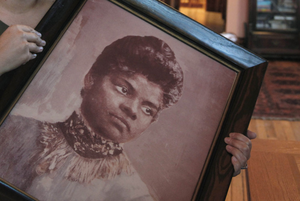 In this Dec. 2, 2011 photo, Michelle Duster, great-granddaughter of civil rights pioneer Ida B. Wells, holds a portrait of Wells. (Charles Rex Arbogast/AP)