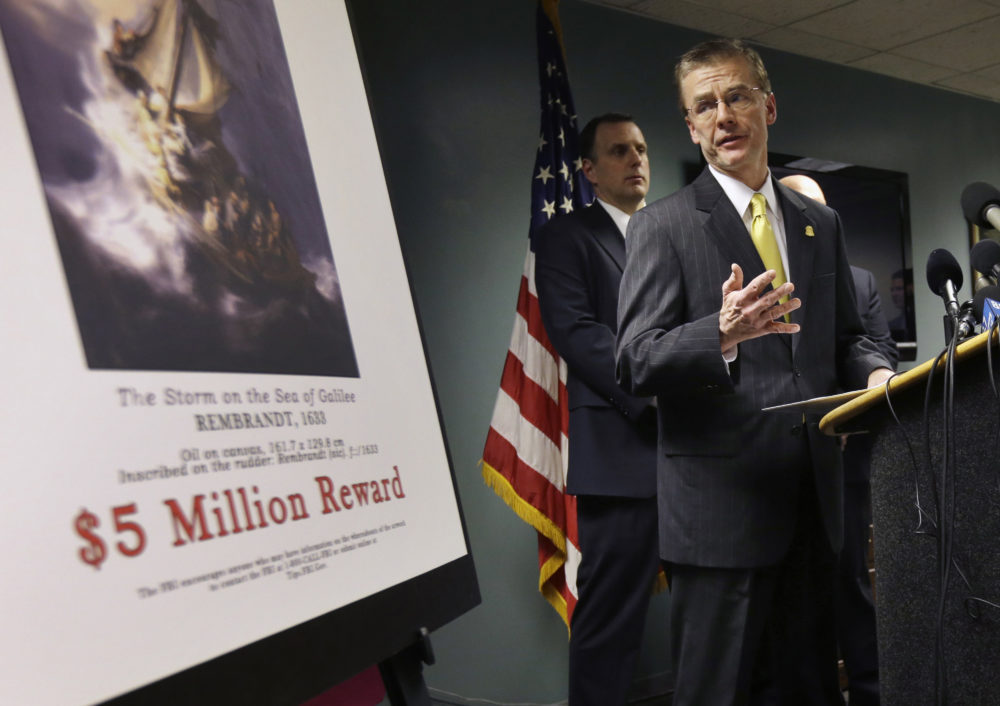 FBI Special Agent in Charge Richard DesLauriers stands next to a poster that shows a Rembrandt painting during a press conference on March 18, 2013. (Steven Senne/AP)