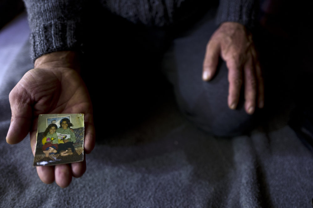 """In this Thursday, Jan. 19, 2017 photo, Ibraheem Ghareeb, 55, a Syrian refugee, shows a photograph of his daughters at his tent in Kalochori refugee camp on the outskirts of the northern Greek city of Thessaloniki.  """"This is the only physical memory that I have left of my late daughter Layla and it never leave my sight."""" Ibraheem said. (Muhammed Muheisen/AP)"""