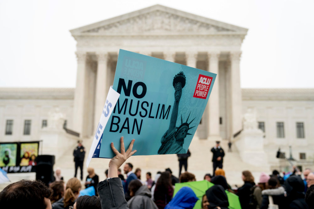 "In this April 25, 2018 file photo, a person holds up a sign that reads ""No Muslim Ban"" during an anti-Muslim ban rally as the Supreme Court hears arguments about wether President Donald Trump's ban on travelers from several mostly Muslim countries violates immigration law or the Constitution in Washington. (Andrew Harnik/AP)"