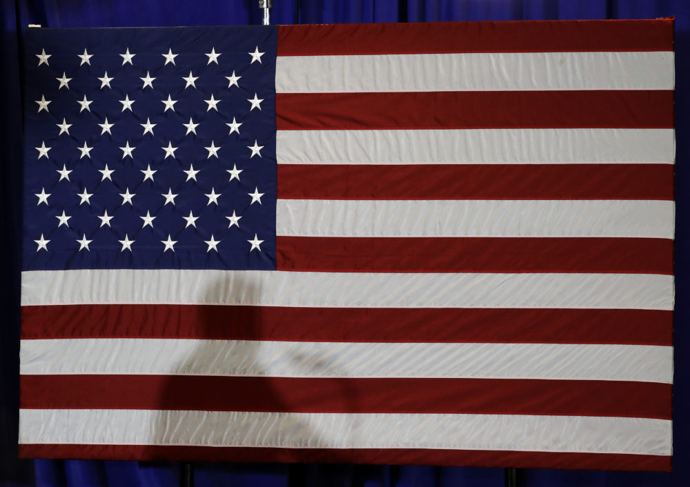 President Trump's shadow is shown on an American flag as he speaks before signing an executive order in Charlotte on Aug. 31, 2018. (Chuck Burton/AP)
