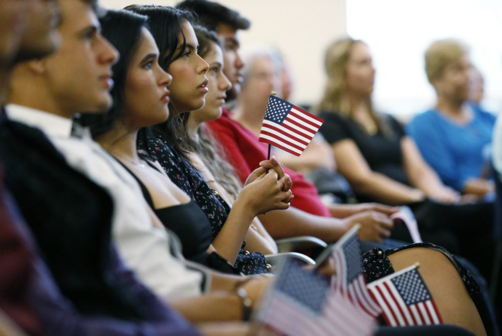 New citizens hold an American flag as they listen during a naturalization ceremony at the U.S. Citizenship and Immigration Services Kendall Field Office, Thursday, Aug. 30, 2018, in Miami. (Wilfredo Lee/AP)