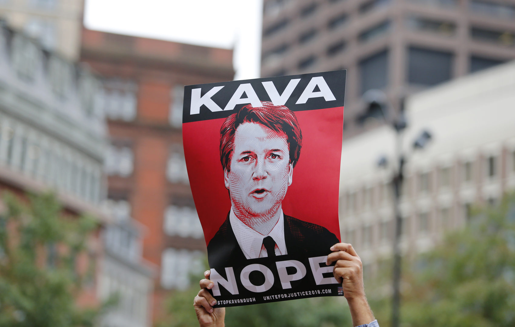 A protester holds a sign in opposition to Judge Brett Kavanaugh at a rally at City Hall ahead of an appearance by Sen. Jeff Flake, R- Ariz. at the Forbes 30 Under 30 Summit, Monday, Oct. 1, 2018, in Boston. (Mary Schwalm/AP)