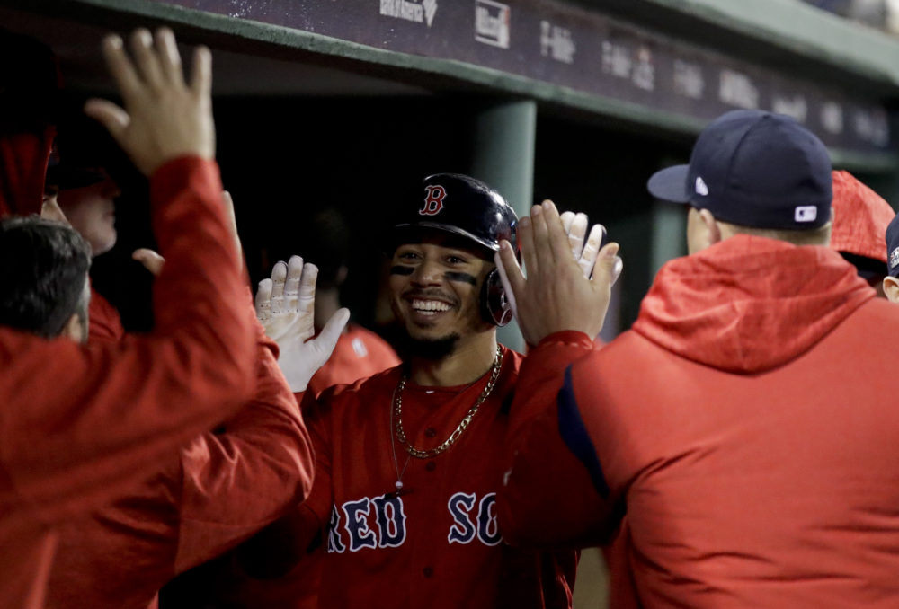 Boston Red Sox's Mookie Betts celebrates in the dugout after scoring of a single by Steve Pearce during the third inning of Game 1 of a baseball American League Division Series against the New York Yankees on Friday, Oct. 5, 2018, in Boston. (Charles Krupa/AP)
