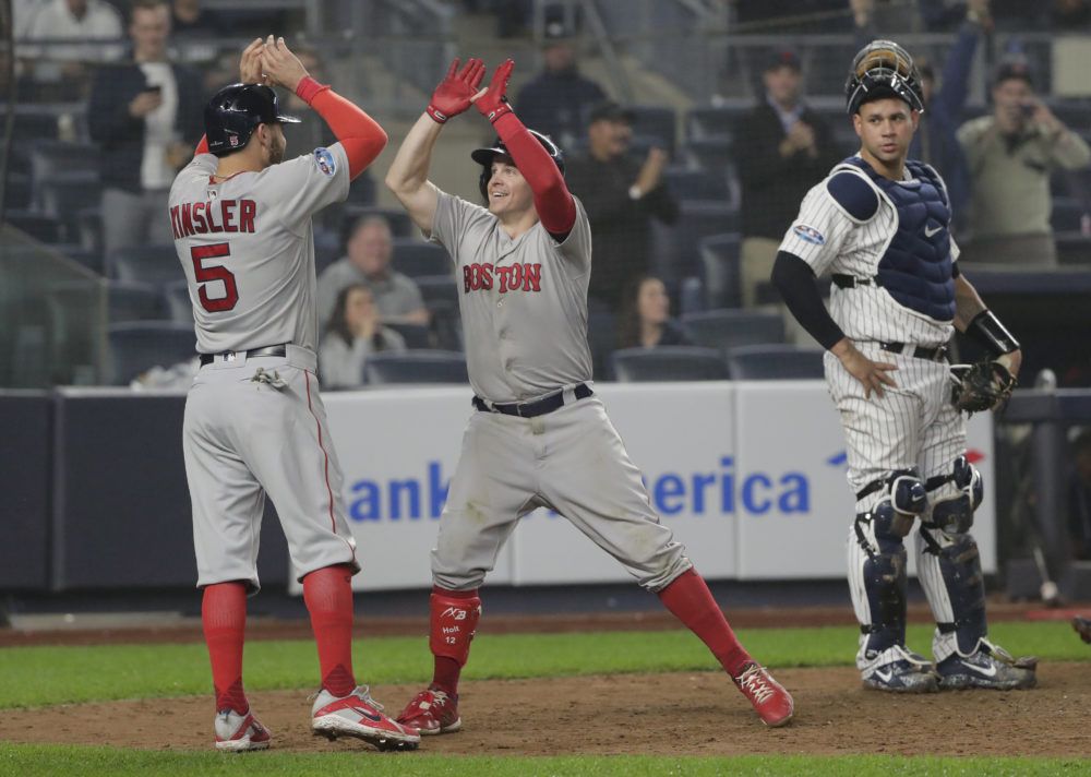 Boston Red Sox's Brock Holt, center, celebrates with Ian Kinsler (5) after hitting a two-run home run against the New York Yankees during the ninth inning of Game 3 of baseball's American League Division Series, Monday, Oct. 8, 2018, in New York. Holt hit for the cycle in the Red Sox's 16-1 win. (Frank Franklin II/AP)