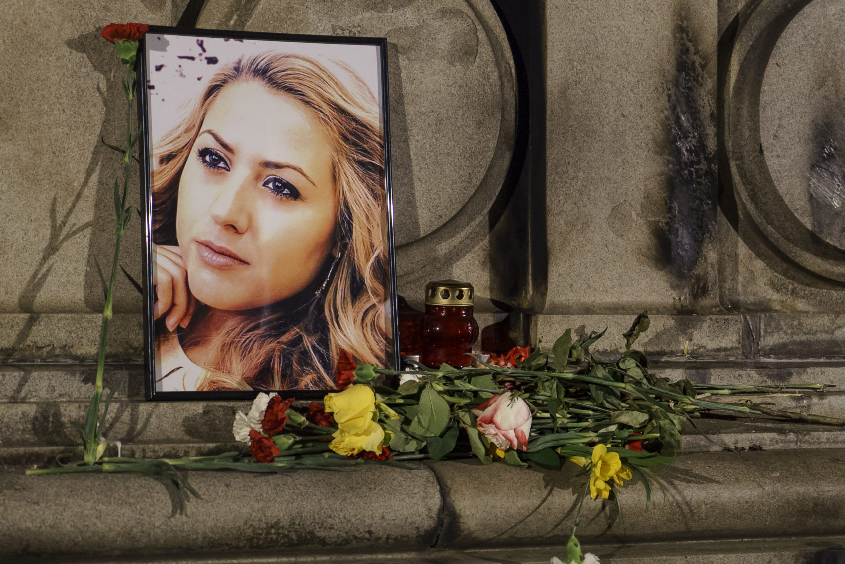A portrait of slain television reporter Viktoria Marinova is placed on the Liberty Monument next to flowers and candles during a vigil in Ruse, Bulgaria, Tuesday, Oct. 9, 2018. (Filip Dvorski/AP)
