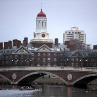 In this March 7, 2017 file photo, rowers paddle down the Charles River past the campus of Harvard University in Cambridge, Mass. A lawsuit alleging racial discrimination against Asian American applicants in Harvard's admissions process is heading to trial in Boston's federal court on Monday, Oct. 15, 2018. Harvard denies any discrimination, saying it considers race as one of many factors when considering applicants. (Charles Krupa/AP File)