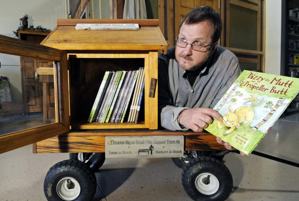In this 2012 file photo, Todd Bol poses with a Little Free Library lending box in Hudson, Wis. Bol, who founded Little Free Library, died Oct. 18, 2018, in a Minnesota hospice of complications from pancreatic cancer. He was 62. (Jim Mone/AP)