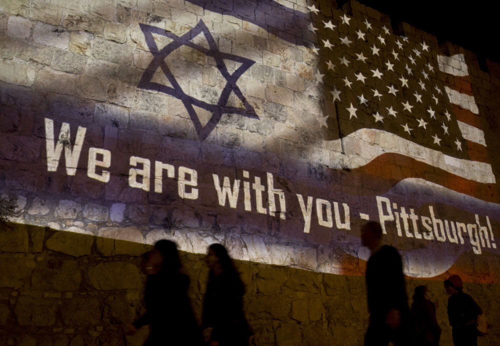 People walk past a projection on the Old City wall in Jerusalem, Sunday, Oct. 28, 2018 in a commemoration of the victims of a deadly shooting at a Pittsburgh synagogue. (Dusan Vranic/AP)