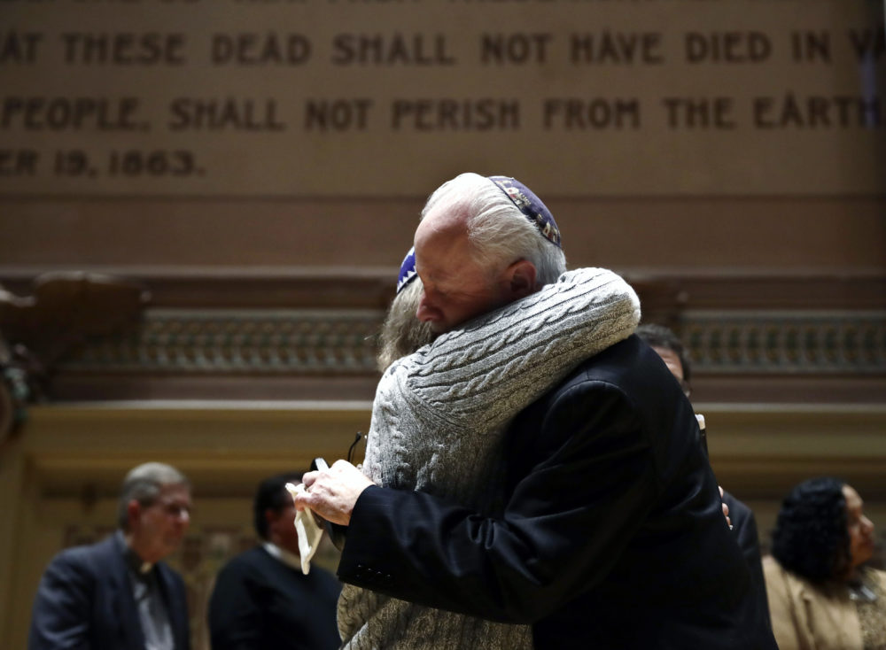 Rabbi Jeffrey Myers of Tree of Life/Or L'Simcha Congregation hugs Rabbi Cheryl Klein of Dor Hadash Congregation on the stage in Soldiers and Sailors Memorial Hall and Museum during a community gathering held in the aftermath of a deadly shooting at the Tree of Life Synagogue in Pittsburgh, Sunday, Oct. 28, 2018. (Matt Rourke/AP)