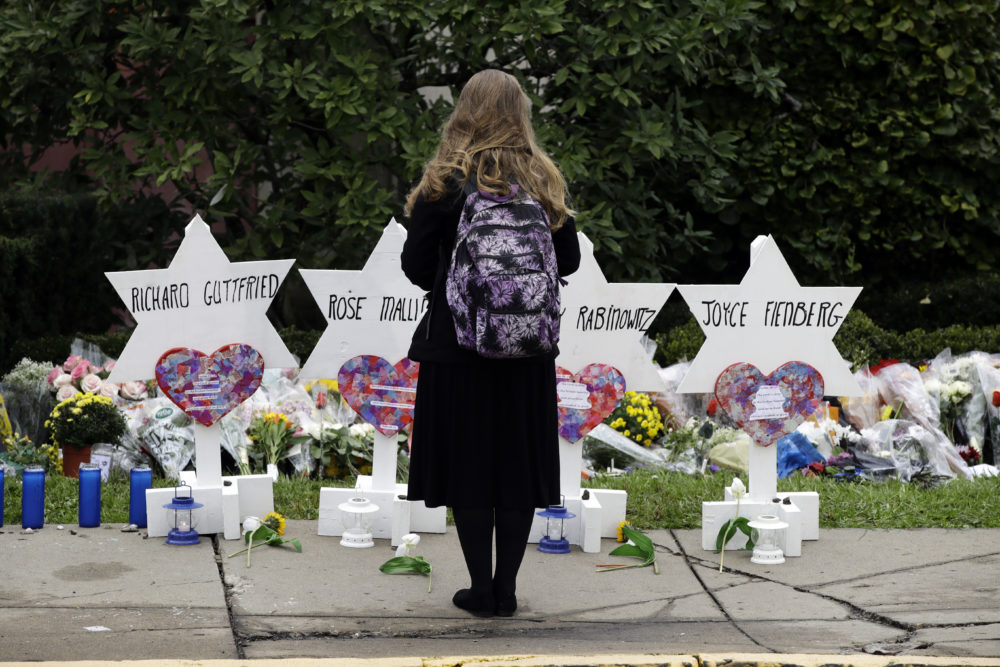 A person stands in front of Stars of David that are displayed in front of the Tree of Life Synagogue with the names of those killed in Saturday's deadly shooting in Pittsburgh, Monday, Oct. 29, 2018. (Matt Rourke/AP)