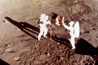"Apollo 11 astronauts Neil Armstrong and Edwin E. ""Buzz"" Aldrin, the first men to land on the moon, plant the U.S. flag on the lunar surface, July 20, 1969.  Photo was made by a 16mm movie camera inside the lunar module, shooting at one frame per second.  (Nasa via AP)"