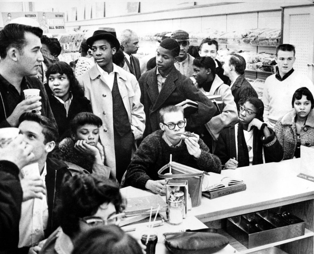 Three African American girls sit next to a white boy at a lunch counter in Portsmouth, Va., as they participate in a sit-down strike in February 1960. The demonstrators are largely students.  (AP Photo)
