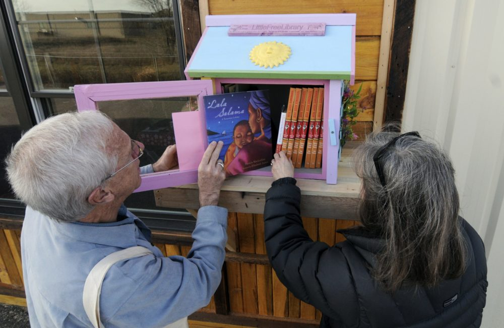In this 2012 photo, Rick Brooks, left, looks through the small glass door as he and Elizabeth Kennedy pose beside one of the Little Free Libraries lending boxes, in Hudson, Wis. (Jim Mone/AP)