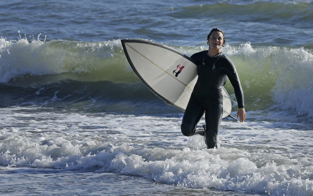 Bianca Valenti walks in from the ocean after surfing waves at Mavericks on Dec. 4, 2015, in Half Moon Bay, Calif. (AP Photo/Ben Margot)