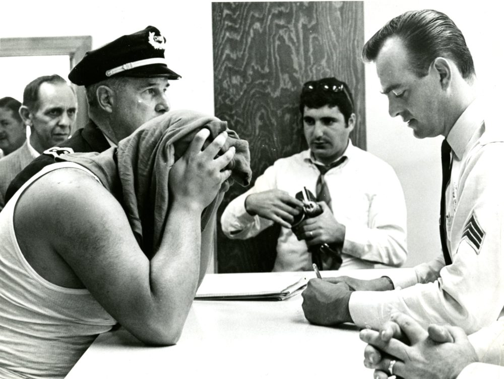 Chief Shea of the Natick police books Bobby Guarante on charges of robbing the First National Bank of Natick in September 1968. (Courtesy William Ryerson/Boston Globe)