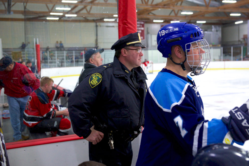 Arlington Police Lt. Rick Pedrini, left, watches a police vs. fire hockey game in 2016. (Courtesy of Melanie Mendez/Wicked Local)