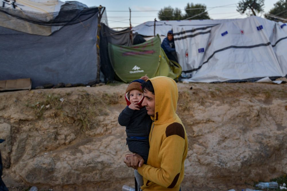 A man carries a child in a camp outside the refugee camp of Moria, in the northern Greek island of Lesbos on September 25, 2018. (Aris Messinis/AFP/Getty Images)