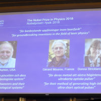 A screen displays portraits of Arthur Ashkin of the United States, Gerard Mourou of France and Donna Strickland of Canada during the announcement of the winners of the 2018 Nobel Prize in Physics at the Royal Swedish Academy of Sciences on Oct. 2, 2018 in Stockholm. (Hanna Franzen/AFP/Getty Images)