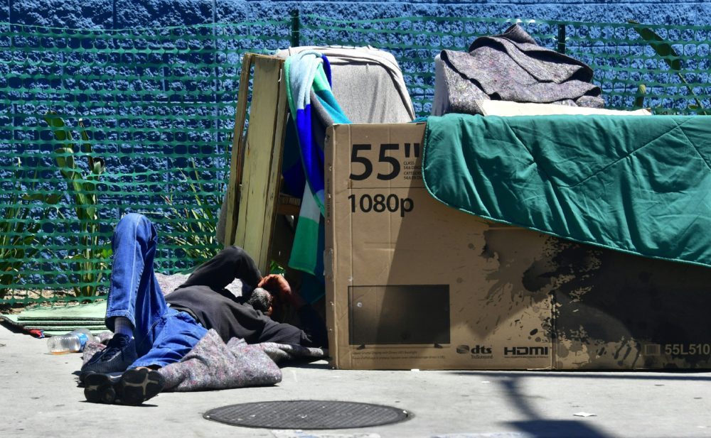 A homeless man sleeps beside his makeshift temporary shelter on a street in downtown Los Angeles in June 2018. (Photo by Frederic J. BROWN / AFP)        (Photo credit should read FREDERIC J. BROWN/AFP/Getty Images)