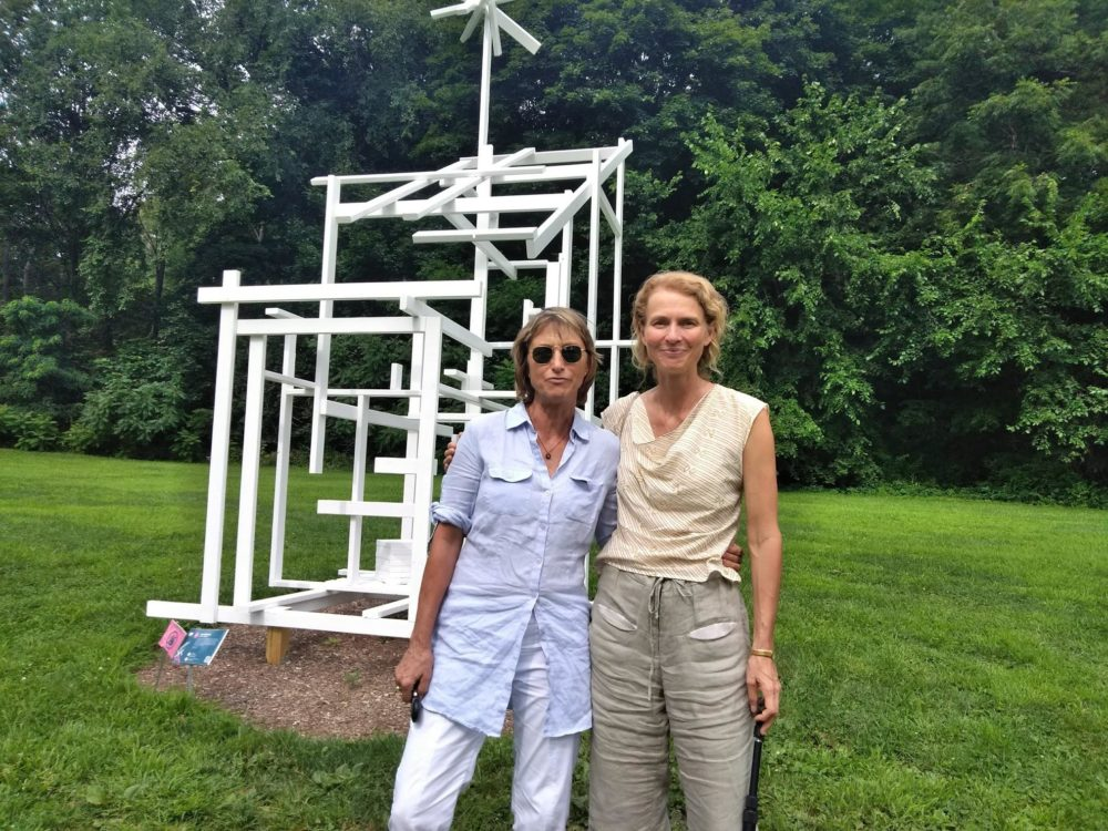 "Curators Eva Fierst, left, and Sandy Litchfield stand with ""Ghost Shed"" by Tom Friedman. The sculpture is installed on land that used to be occupied by frat houses. (Jill Kaufman/NEPR)"