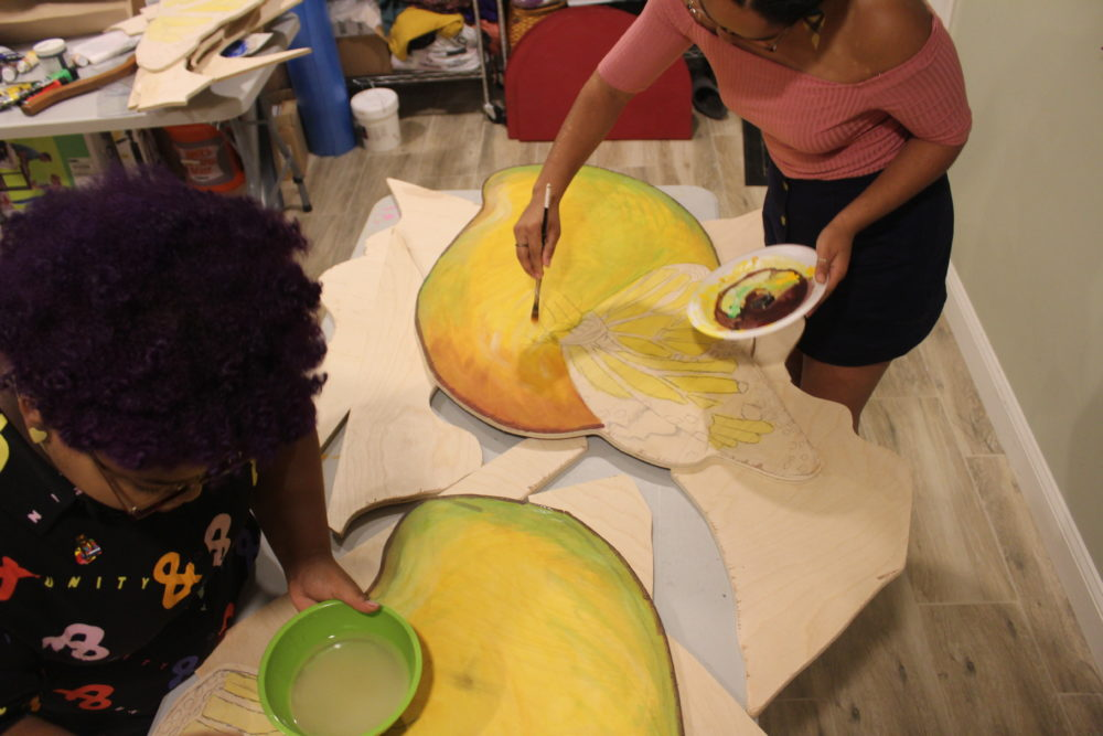 "Artists Chanel Thervil, left, and Iris Lapaix prepare for ""Mariposas and Mangos."" (Arielle Gray for WBUR)"