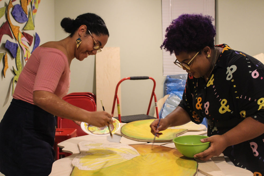 "Artists Iris Lapaix and Chanel Thervil prepare for ""Mariposas and Mangos."" (Arielle Gray for WBUR)"