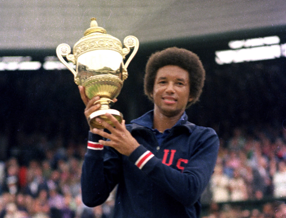 Arthur Ashe hoists the 1975 Wimbledon trophy after beating the highly favored Jimmy Connors. (AP Photo)
