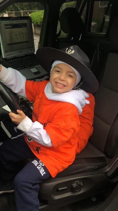 Cristopher Chavarria poses in the front seat of a police cruiser after a community walk in support of his family. (Courtesy Yohana Velasquez)