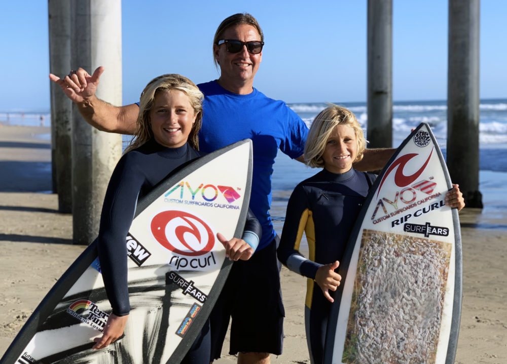 Peter Romaniuk takes his 8-year-old son Petey and 12-year-old daughter Juliana to Huntington Beach to catch some waves. Both of his kids have been surfing since they were two. (Chris Bentley/Here & Now)